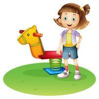 Ein Mädchen, das neben einem Pferdefrühlingsspielzeug steht vektor