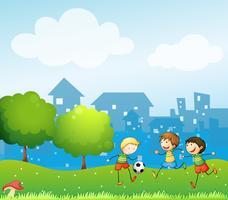 Tre barn leker fotboll i backen vektor