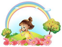 En leende tjej i trädgården med rosa blommande blommor