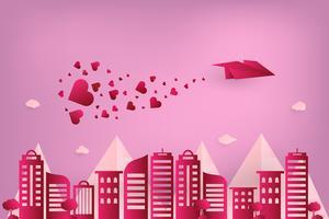 Konzept Liebe und Valentinstag. Origamipapierflugzeug, das über städtische Stadt mit Herz fliegt, streuen am Himmel. Papierkunststil.