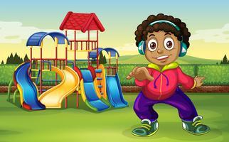 En pojke lyssnar på musik på lekplatsen