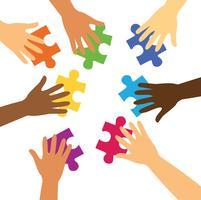 många händer som håller färgglada pusselbitar