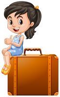 Liten flicka sitter på en resväska
