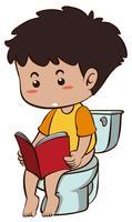 Pojke läser bok när man går på toaletten