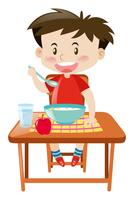 Junge, der auf dem Tisch von der Schüssel isst vektor