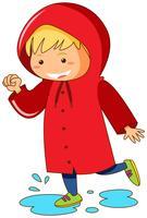Kind im roten Regenmantel, der in Pfützen springt