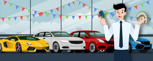 Glad affärsman, säljare står och håller ett kreditkort och pengar framför grupp lyxbil som parkerar i stort showroom i staden.
