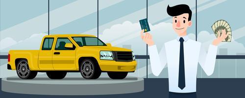 Glad affärsman, säljare står och håller ett kreditkort och pengar framför gula pickup truck som parkerar i stort showroom i staden.