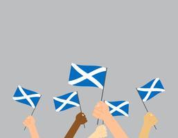 Vector die Illustrationshände, die Schottland-Flaggen auf grauem Hintergrund halten