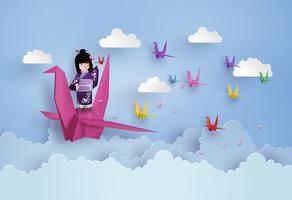 Japanische Mädchen, die Nationalkostüm und Origamivogelfliegen auf dem Himmel mit clound tragen.