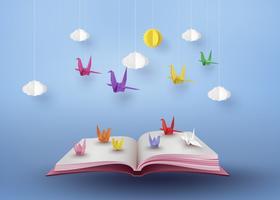Origami gemacht buntes Papier Vogel fliegt über offenes Buch