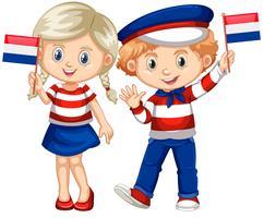 Glad pojke och flicka som håller flagga i Nederländerna