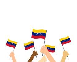 Vector Illustration von den Händen, die Venezuela-Flaggen halten, die auf weißem Hintergrund lokalisiert werden