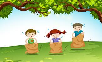 Tre barn som leker i parken