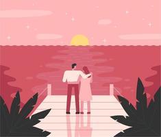 Romantiska par som står vid havet vid solnedgången