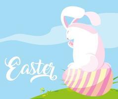 süßes Kaninchen mit Ei von Ostern im Gras
