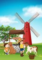Kinder und Tiere auf dem Hof mit Windmühle vektor