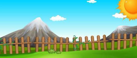 Szene mit Bergen und Feldern mit Zaun
