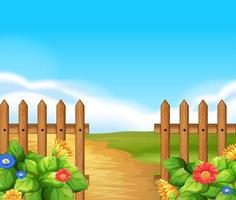 Plats med trästaket och fält med blommor