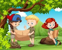 Tre barn som läser kartor i skogen