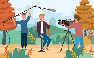 Manlig reporter och kameramännen i parken