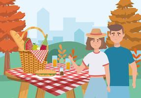 Kvinna- och manpar som har picknick på bordet