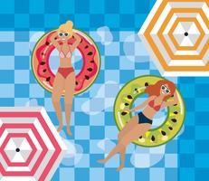 Två kvinnor som kopplar av i flottör i poolen