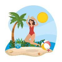 Die Frau springend auf Strand im Hut und im Badeanzug