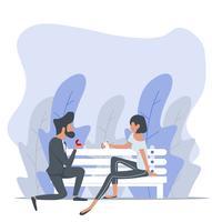 Man som föreslår en kvinna som sitter på bänken