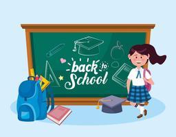 Kvinnlig student med tillbaka till skolmeddelandet på svarta tavlan
