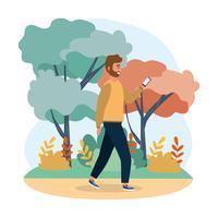 Mann mit dem Bart, der Smartphone im Park betrachtet