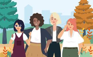 Unga olika kvinnor i casual kläder i stadspark