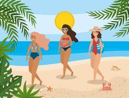 Kvinnor i baddräkter som går på stranden