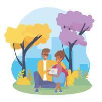 Junge Paare, die mit Tablette im Park sitzen