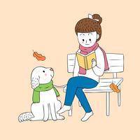 Herbstfrau, die ein Buch und einen Hund liest