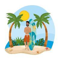 Man i baddräkt som står vid surfbräda på stranden
