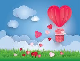 Herzförmiger Heißluftballon, der in Himmel mit Wolken fliegt