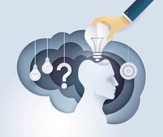 Hand som sätter en glödlampa i mänskligt huvud