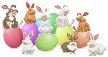 viele Kaninchen sitzen auf bunten Eiern vektor