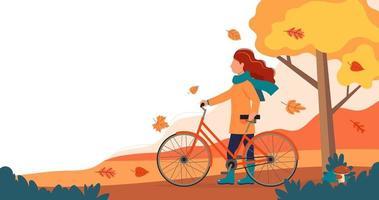 flicka stående med cykel i parken på hösten