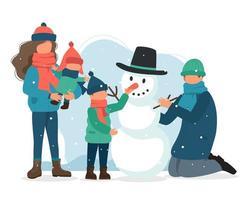 mamma som håller barn och familj som gör snögubbe