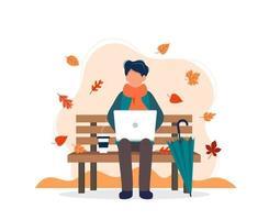 man med laptop på bänken på hösten