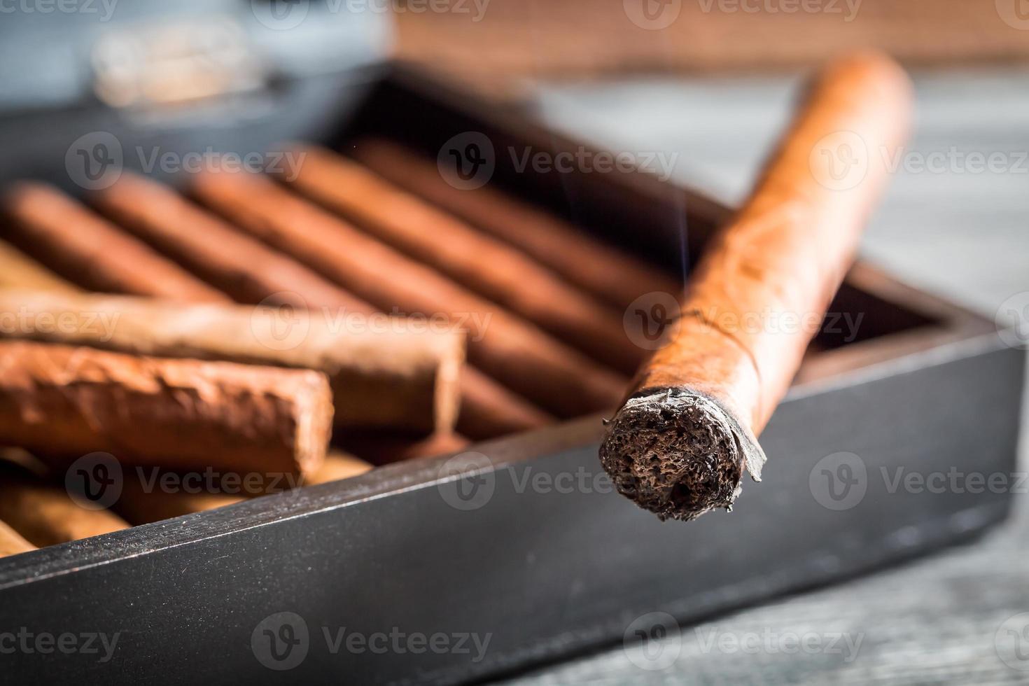 Gros plan du cigare brûlant de fumée photo