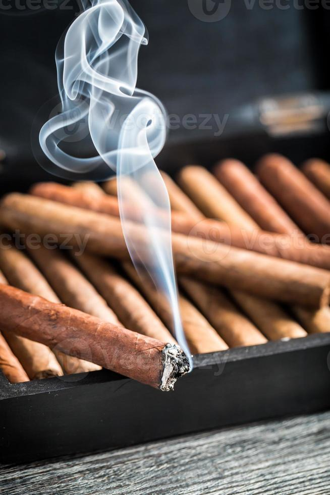 Cigare brûlant sur une cave à cigares en bois pleine de cigares photo