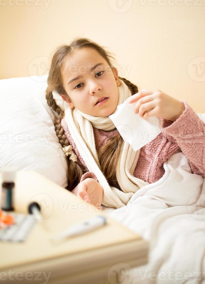fille malade couché dans son lit et tenant du papier absorbant photo