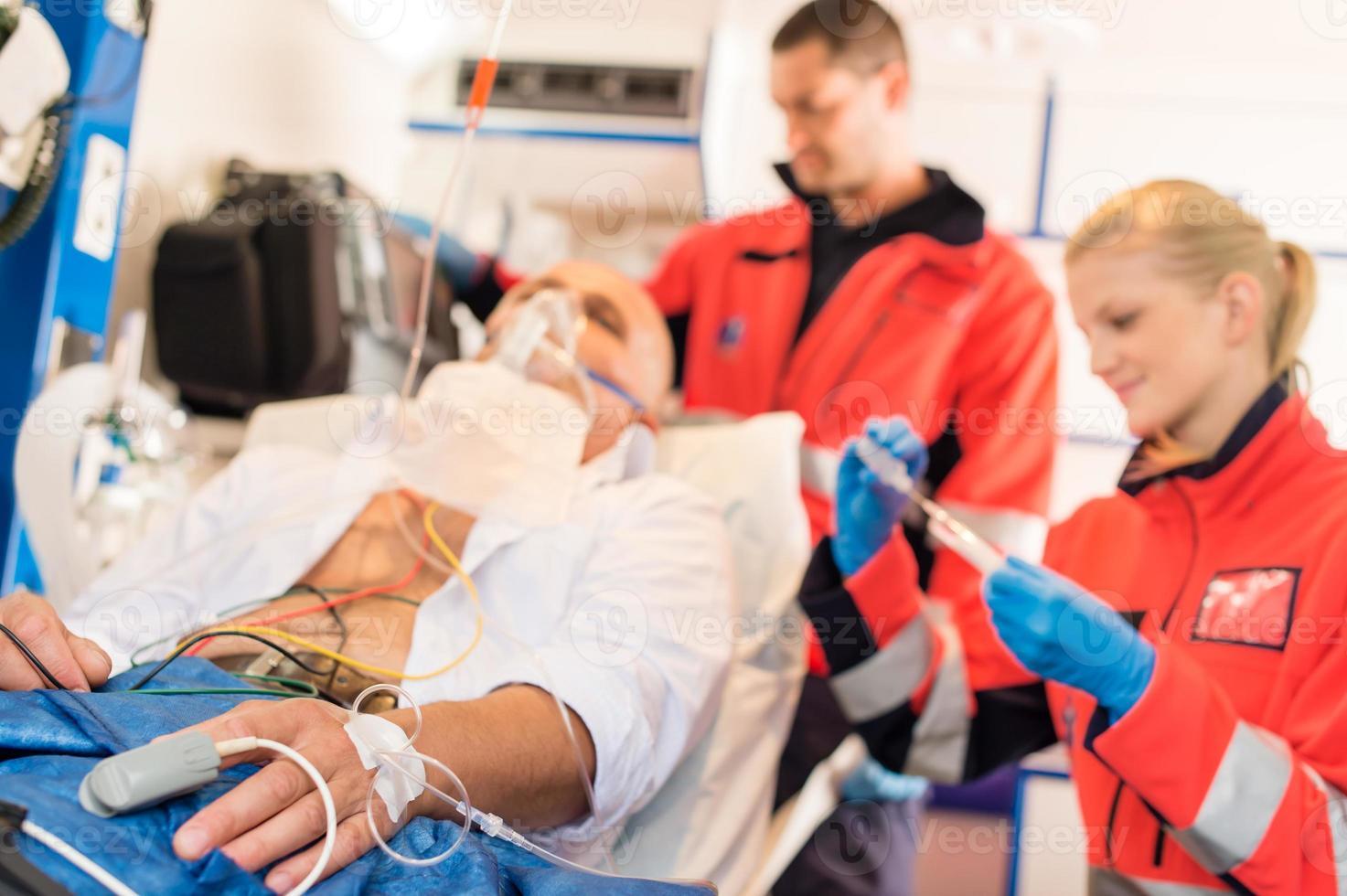 patient malade traité par des ambulanciers paramédicaux dans une ambulance photo