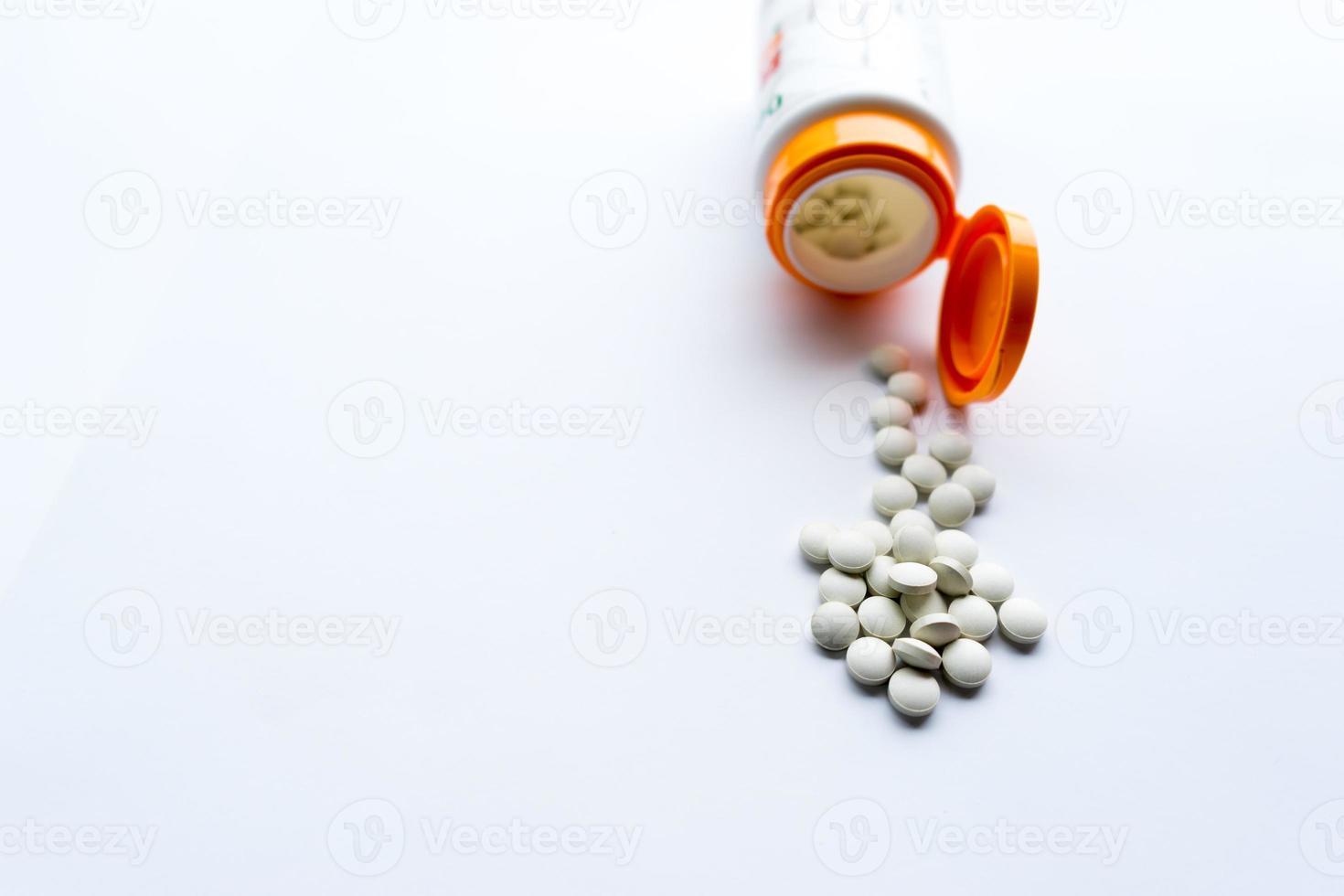 pilules sortant de flacon de médicament, sur fond blanc photo
