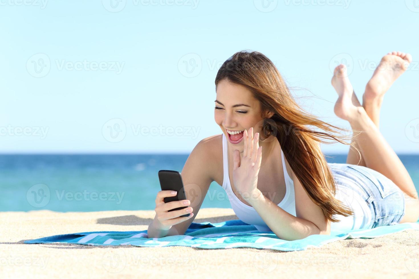 Adolescente agitant lors d'un appel vidéo sur un téléphone intelligent photo