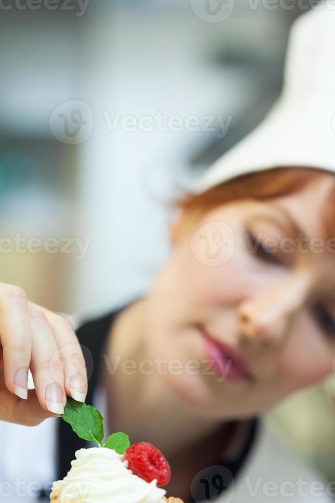 Chef cuisinier concentré mettant la feuille de menthe sur le petit gâteau photo