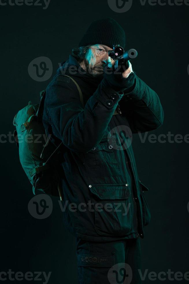 tireur d'élite avec barbe en noir tenant le pistolet. tourné en studio. photo